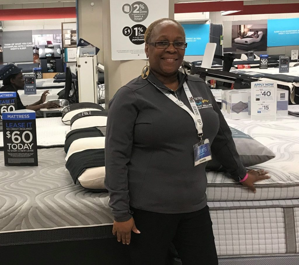 Sears mattress sales associate Annette Thomas stands in front of a display of mattresses.