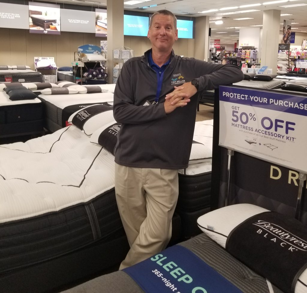 Sales associate Robert Cothern stands in front of a display of mattresses at a Sears store.