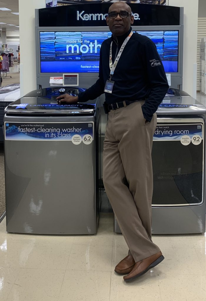 Sears associate stands in front of a gray Kenmore elite washer/dryer combo.