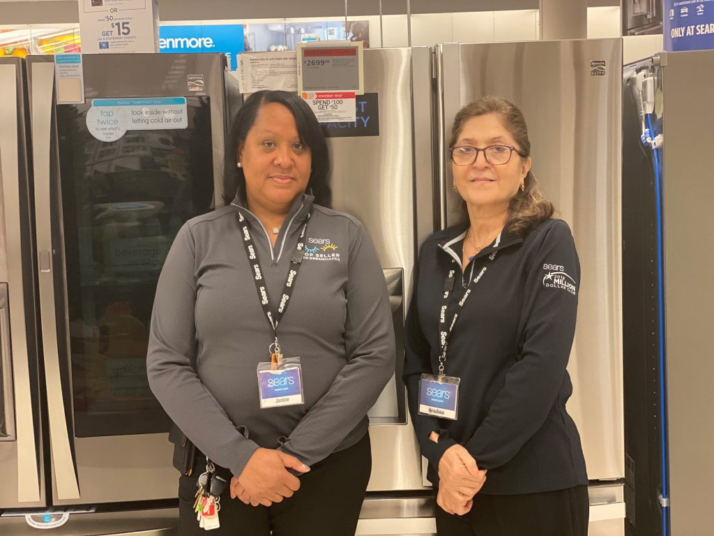 Two Sears associates stand in front of stainless steel appliances at a Sears store