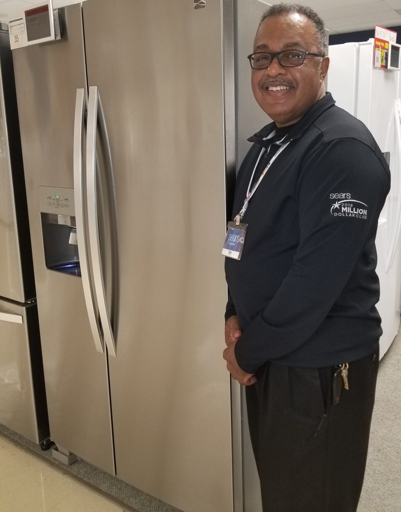 Sears sales associate Tom Wiggins stands in front of a stainless steel refrigerator at Sears.