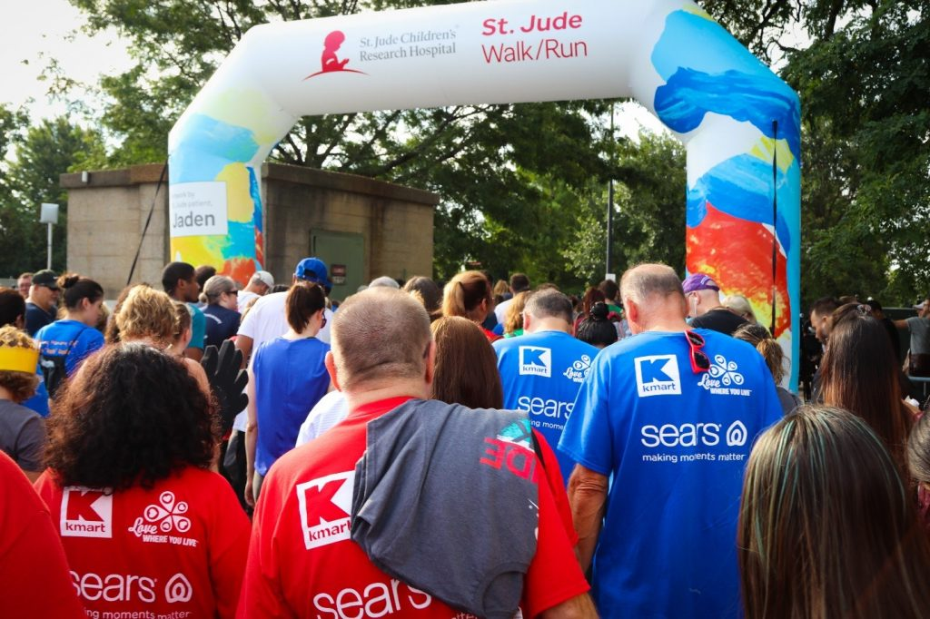 Members of the Kmart and Sears St. Jude Walk/Run team join a crowd of walkers crossing the start line to the 2019 walk run event wearing red and blue T-shirts.