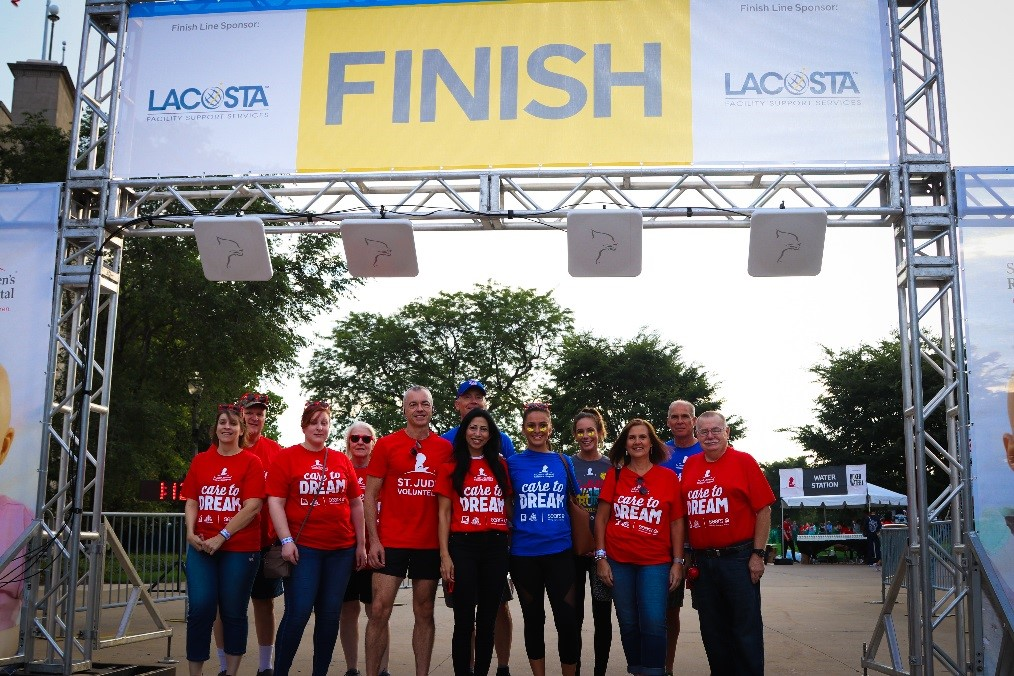 Seven Sears and Kmart associates stand in a line smiling under the St. Jude Walk/Run finish line.