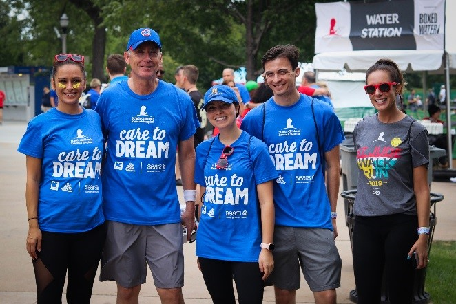 Associates wearing Sears Care to Dream T-shirts smile as they prepare for the event.