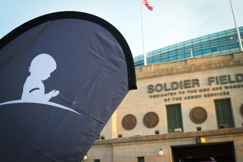 A St. Jude banner waves in the wind against the backdrop of Soldier Field in Chicago.