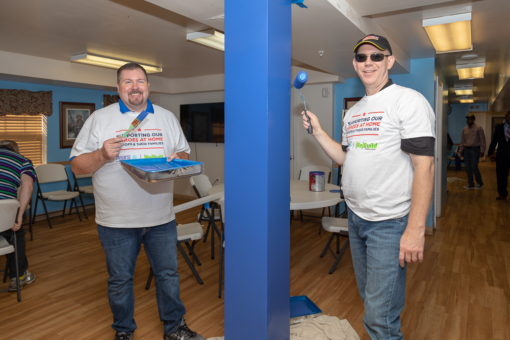 Two volunteers smile for the camera after painting a blue support beam. One is holding a brush and paint pan of blue paint matching the beam while the other is painting with a roller. Both are wearing Sears Heroes at Home and Rebuilding Together T-shirts.