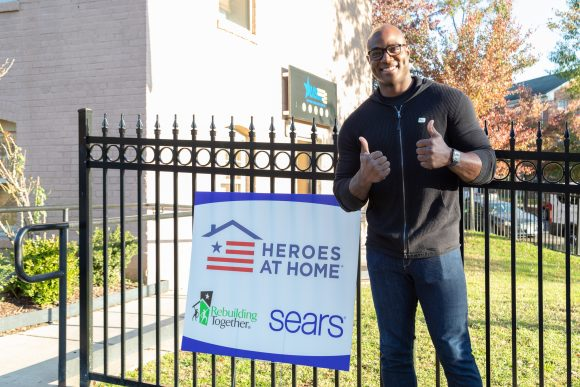 DeMarcus Ware gives two thumbs up in front of a project sign for Rebuilding Together and Heroes at Home completed in partnership with Sears.