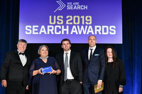 Members of the Sears Home Services SEM/SEO team stand on a stage to receive their US Search Award.